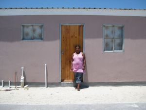Gloria Rudolf in front of her unoccupied house